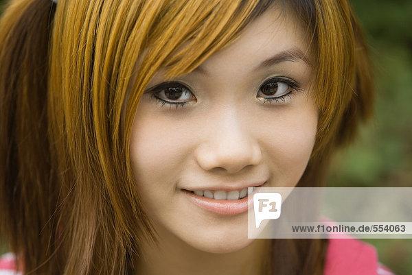 Junge Frau  lächelnd vor der Kamera  Nahaufnahme  Porträt