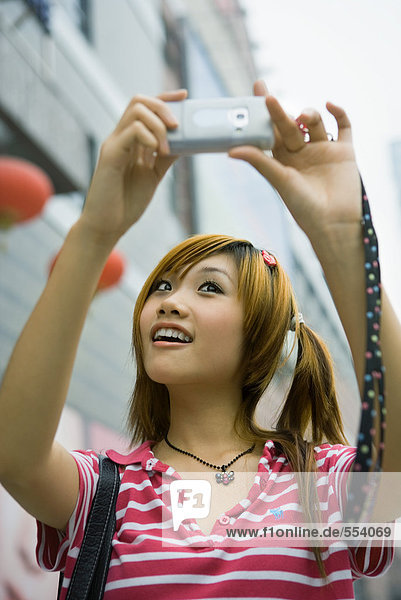 Junge Frau fotografiert sich selbst mit dem Handy