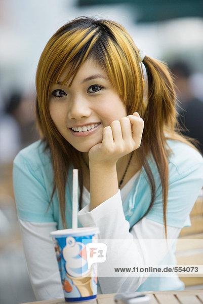 Junge Frau sitzend mit Fast-Food-Getränk  lächelnd vor der Kamera