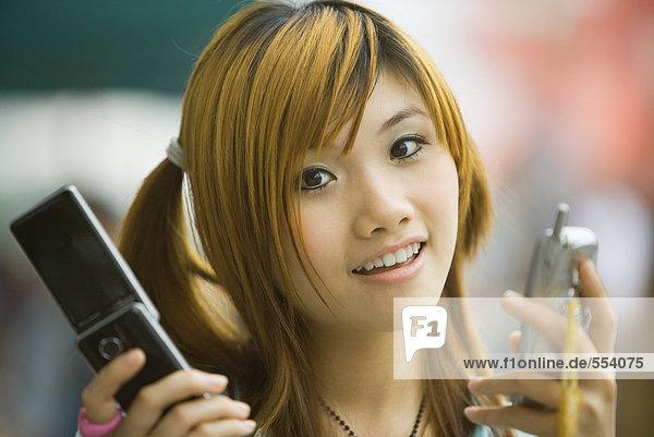 Junge Frau hält zwei Handys in der Hand und schaut in die Kamera.
