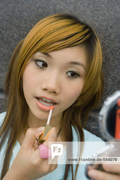 Junge Frau  die Lipgloss und Mund aufträgt.