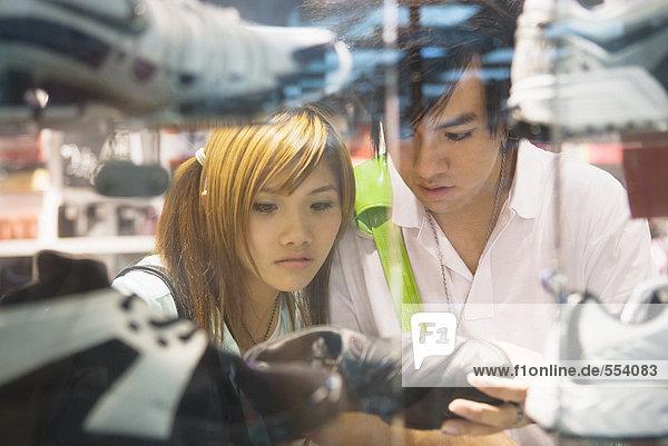 Junges Paar sucht Sportschuhe im Geschäft