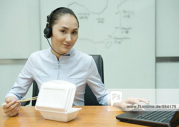 Geschäftsfrau  die Essen zum Mitnehmen isst  ein Headset trägt und einen Laptop benutzt.