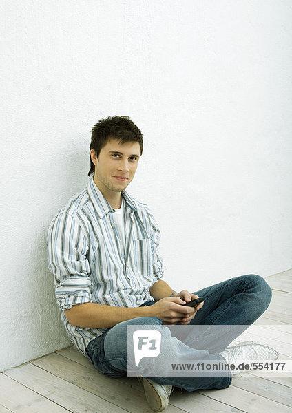 Junger Mann auf dem Boden sitzend  Handy haltend