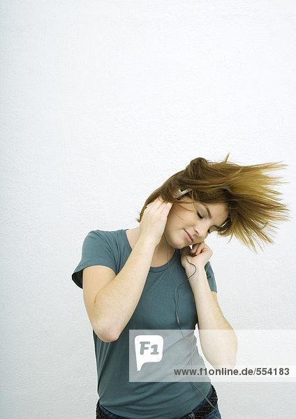 Junge Frau hört Kopfhörer mit geschlossenen Augen  schwingende Haare