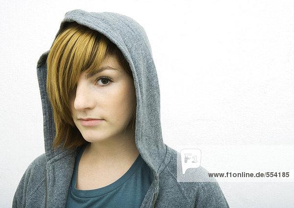 Junge Frau mit Kapuze  Blick in die Kamera  Porträt