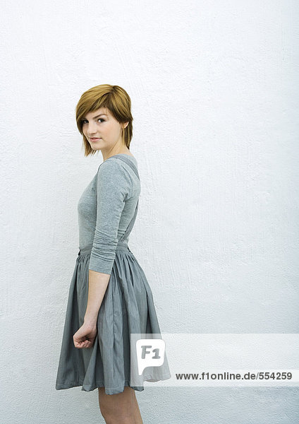 Young woman standing  looking at camera  side view  portrait