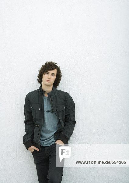 Junger Mann an der Wand lehnend mit Händen in den Taschen  Portrait  weißer Hintergrund