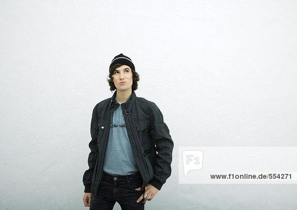 Junger Mann mit Strickmütze und Jacke  aufblickend