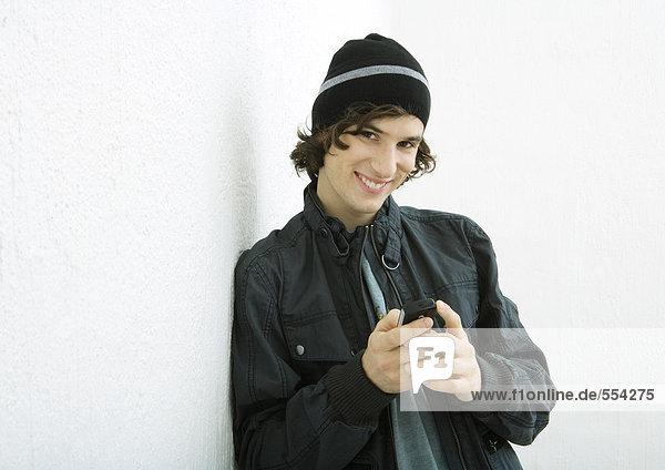 Junger Mann hält Handy  lächelt in die Kamera  weißer Hintergrund