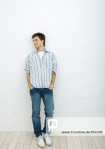 Junger Mann stehend mit den Händen in den Taschen  wegschauend  Ganzkörperporträt