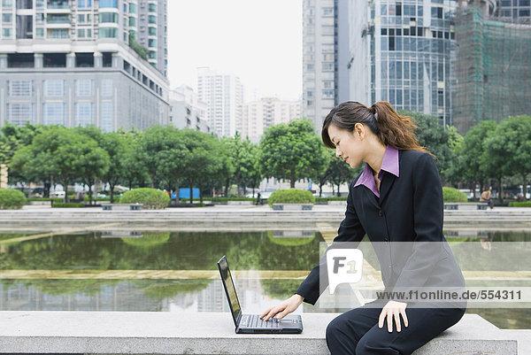 Geschäftsfrau mit Laptop am Wasser im Büropark