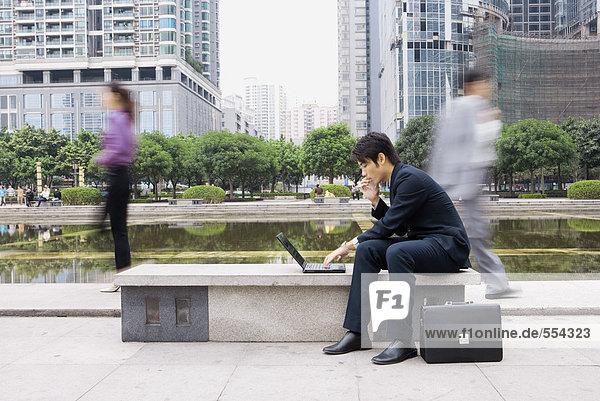 Geschäftsmann mit Laptop im Büropark  Passanten verschwommen im Hintergrund