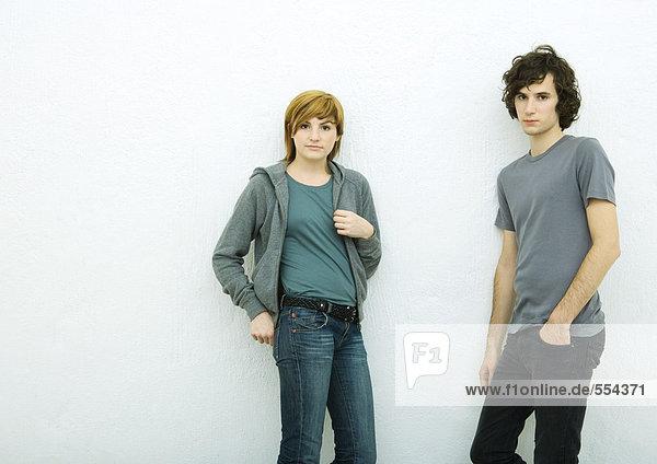 Junger Mann und junge Frau lehnen sich an die Wand  schauen in die Kamera  weißer Hintergrund