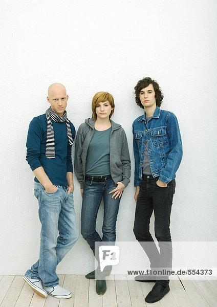 Drei junge Erwachsene  die sich an die Wand lehnen  auf die Kamera schauen  Portrait in voller Länge  weißer Hintergrund