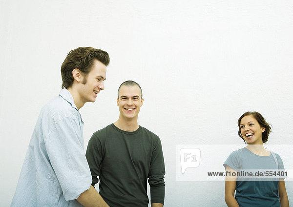 Drei junge Erwachsene,  lachend,  weißer Hintergrund