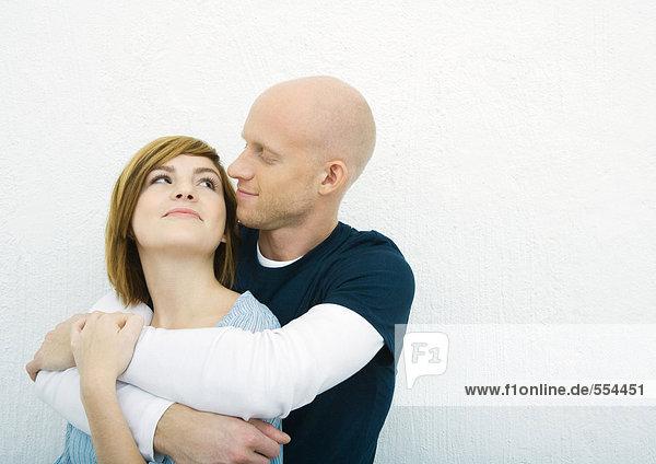 Junges Paar  Mann hält Frau von hinten  schaut sich gegenseitig an