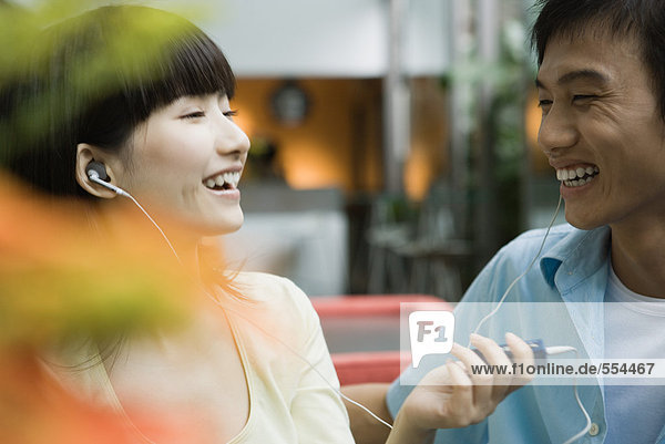 Young couple sharing earphones  laughing