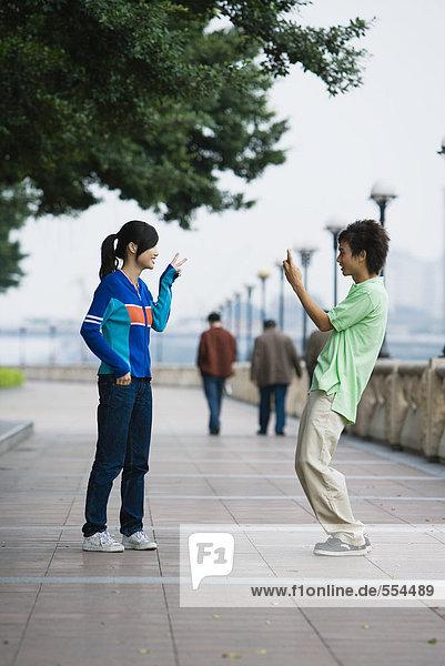 Junger Mann beim Fotografieren einer Freundin