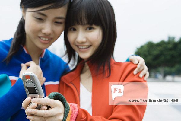 Zwei junge Frauen  die zusammen auf das Handy schauen.