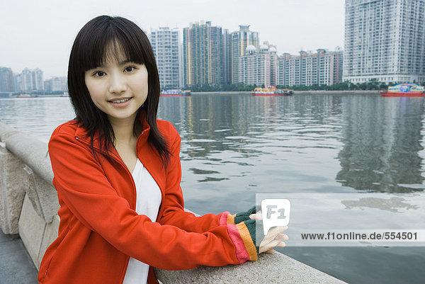 Junge Frau am Fluss stehend  Hochhäuser im Hintergrund