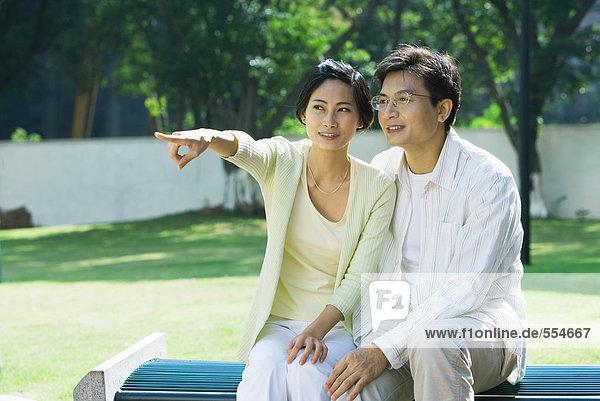 Paar auf Bank sitzend  Frau aus dem Rahmen zeigend
