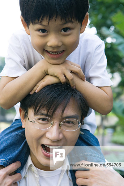 Boy riding on father's shoulders  front view  smiling at camera
