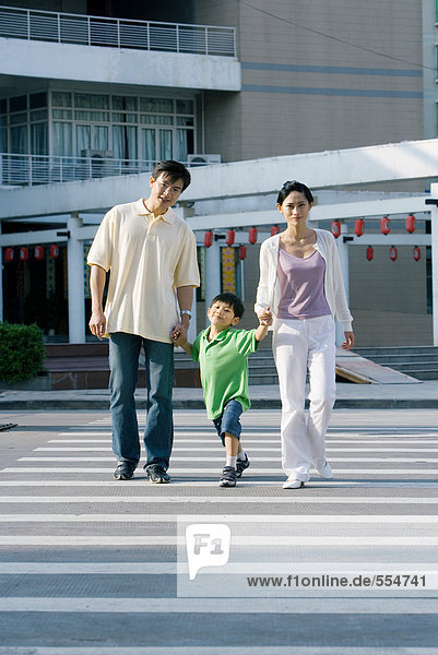 Boy crossing crosswalk  hand in hand with parents  full length