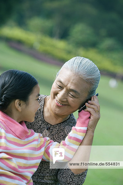 Girl with grandmother  holding cell phone to ear