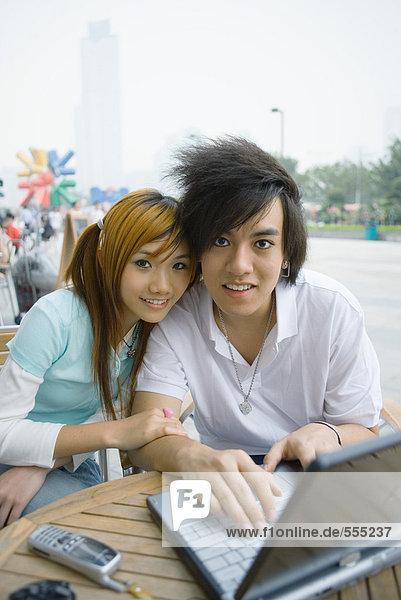 Teenager-Paar im Freien sitzend  mit Laptop  lächelnd vor der Kamera