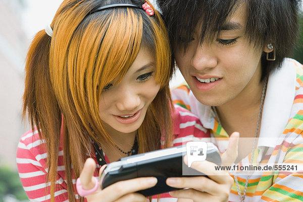 Teenager-Paar mit tragbarem Videospiel