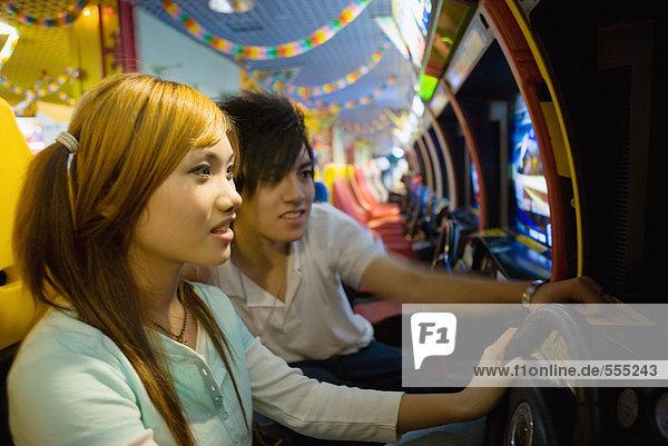 Teenager-Paar beim Spielen in der Videospielhalle