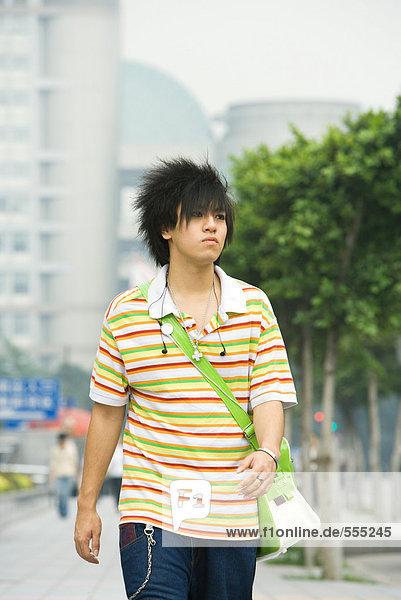 Teenager-Junge beim Spazierengehen in der Stadt