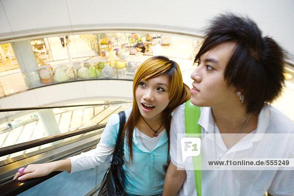Teenager-Paar auf Rolltreppe im Einkaufszentrum
