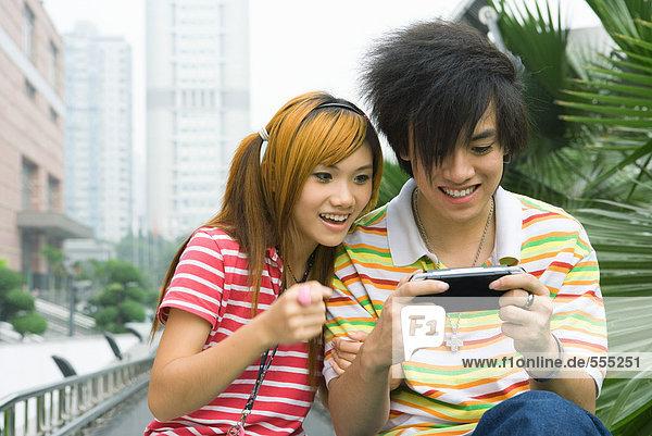 Teenager-Paar spielt mit Handheld-Videospiel  draußen