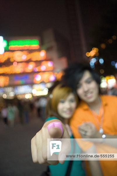 Teenager-Paar  konzentrieren Sie sich auf den Finger des Mädchens  der auf die Kamera zeigt.