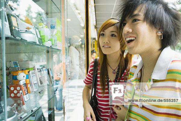 Teenager-Paar schaut zum Schaufenster