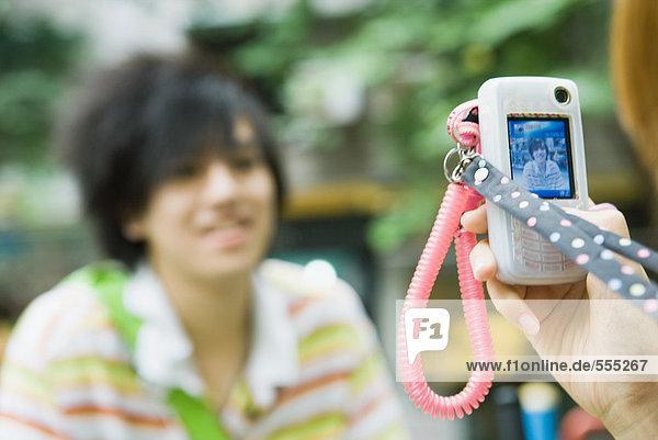 Teenager-Junge  der mit dem Handy fotografiert wurde.