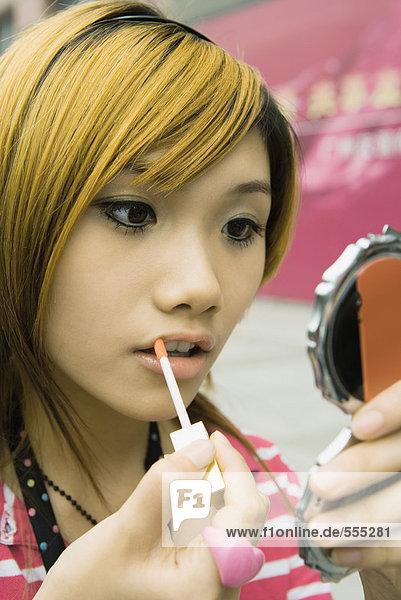 Teenager-Mädchen  das Lipgloss aufträgt  Mund