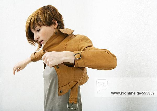 Junge Frau beim Anziehen der Jacke