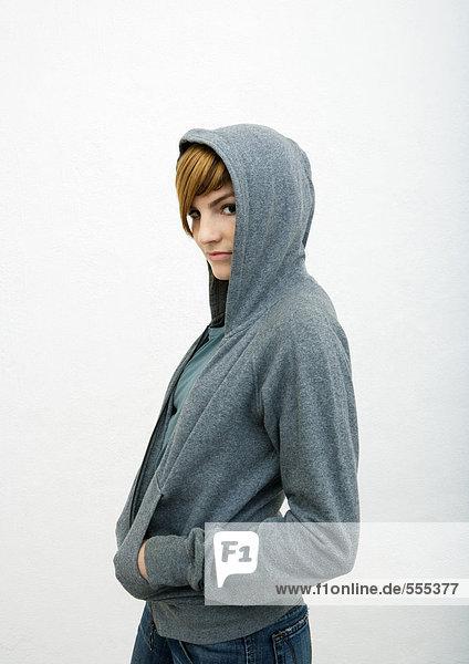 Junge Frau stehend mit Händen in Sweatshirt Taschen