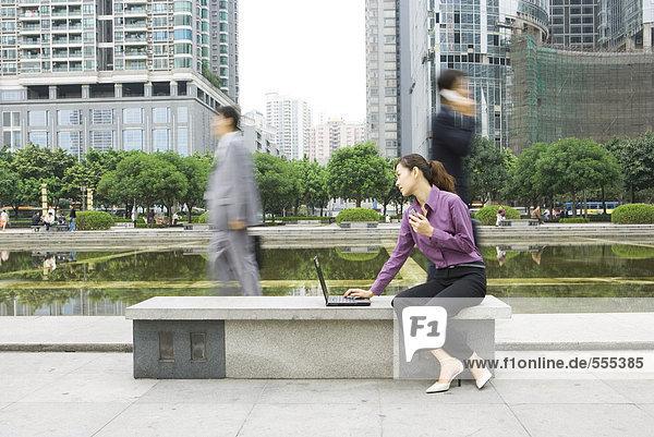 Junge Frau mit Laptop im Freien auf der Parkbank im Büro