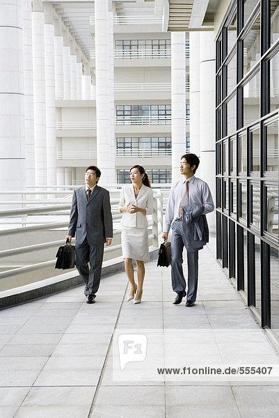 Drei junge Führungskräfte gehen Seite an Seite mit dem Bürogebäude