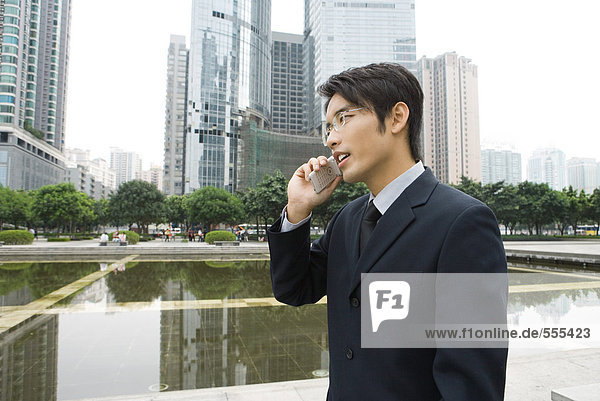 Businessman using cell phone in office park  side view