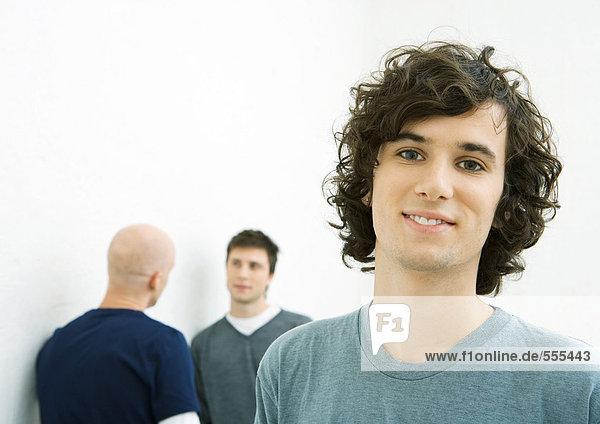 Junger Mann lächelt in die Kamera  zwei junge Männer sprechen im Hintergrund