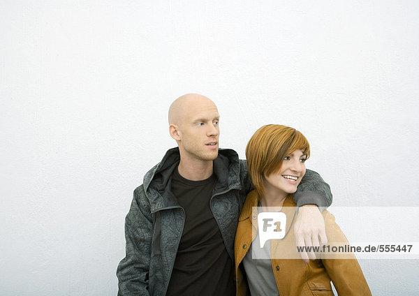 Junges Paar  Mann mit Arm um die Schulter der Frau  beide schauend weg