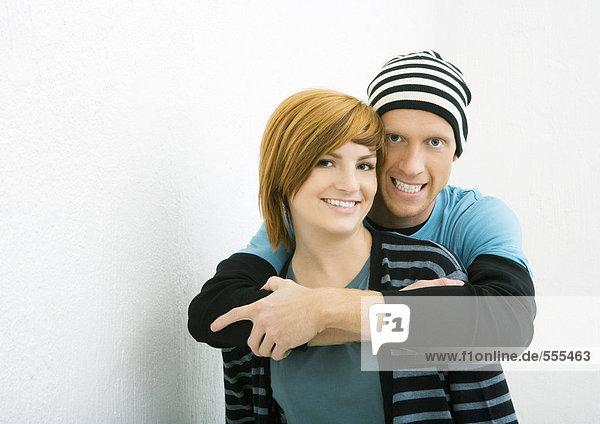 Junges Paar  Mann steht hinter einer Frau mit Armen um sie herum  beide lächeln in die Kamera.