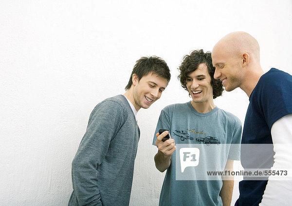 Junger Mann zeigt zwei männliche Freunde Handy