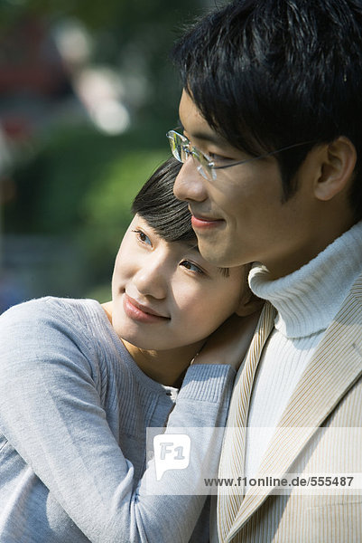 Junges Paar  Frau lehnt sich mit dem Kopf auf die Schulter des Mannes  beide schauen weg.