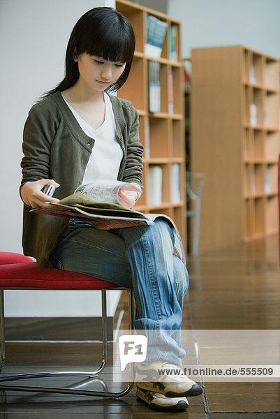 Junge Frau studiert in der Bibliothek
